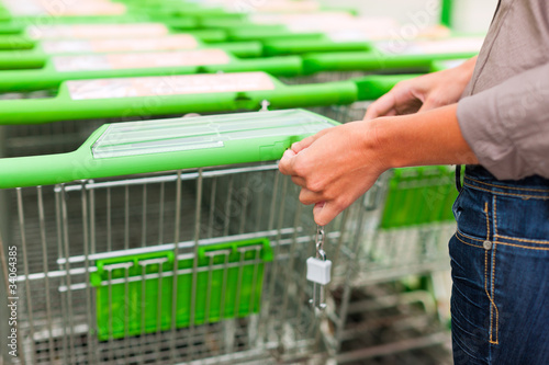 Woman in supermarket with shopping cart