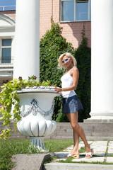 Блондинка позирует на фоне колонн.