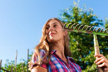 Gartenarbeit im Sommer - Frau mit Rechen