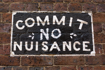 Commit No Nuisance Sign on brick wall