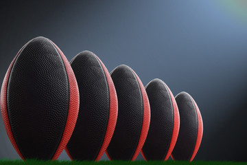 American fotballs in a row on a dark-blue background and light