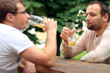 Two male friends talking and drinking beer, outdoors