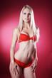 Blonde Frau in roter Wäsche blickt hübsch, Hände unten