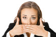 Businesswoman covering with hands her mouth, isolated