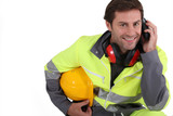 Workman in protective gear with mobile phone poster