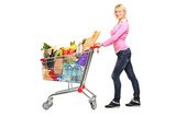 Young female pushing a shopping cart full with groceries