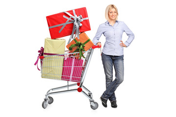 Woman posing next to a shopping cart full with gifts