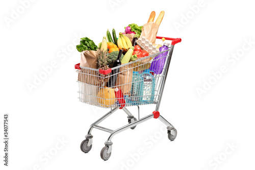 A shopping cart full with various groceries