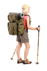 Woman with backpack and hiking poles posing
