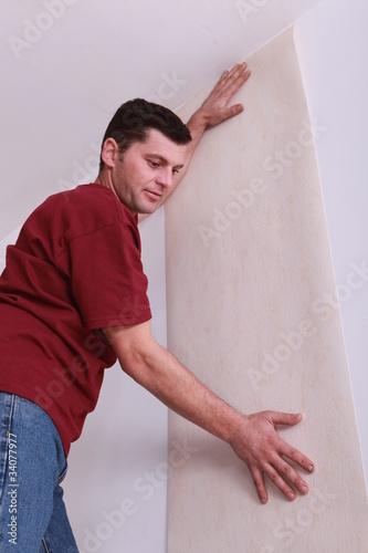 Man wallpapering room