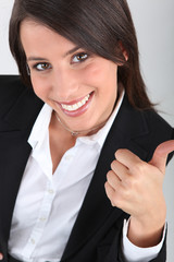 Woman in a suit giving the thumbs up