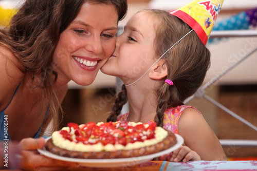 Daughter kissing mommy at birthday party