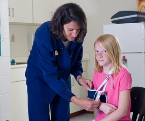 School nurse checking sling for broken arm