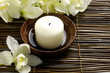 bowl of candle with orchid on mat