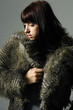 Attractive woman in fur coat on gray background