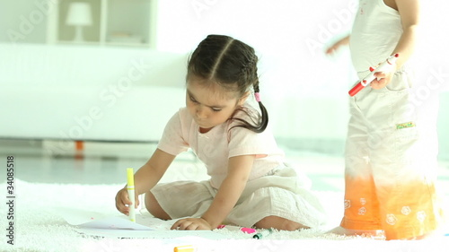 Two little girls sitting on floor and drawing