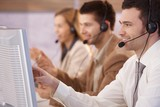 Young people working in callcenter smiling