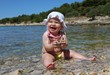 Baby girl playing with pebbles at the Adriatic beach