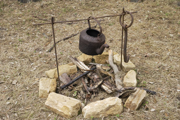 Old rusty kettle over open fire