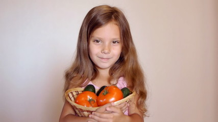 Little girl with tomatoes and cucumbers and smiles.