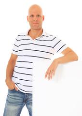 Mann mittleren Alters lehnt locker an weißer Wand