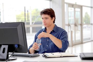 Office worker drinking water in front of desktop computer