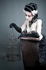 Junge Frau mit leerem Vogelkäfig