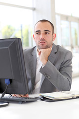 Businessman in front of desktop computer with thoughtful look