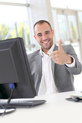 Happy businessman showing thumbs up