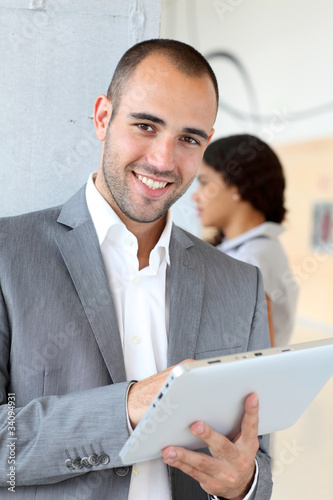 Young businessman using electronic tablet