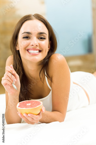 Smiling beautiful woman eating grapefruit on bed, at home