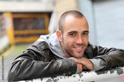 Smiling young man with leather jacket in town