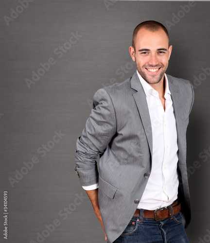 Cool businessman standing on grey background
