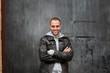 Man with leather jacket standing on metal door