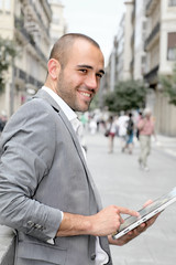 Man with suit jacket using touchpad in town