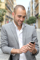 Relaxed businessman with mobile phone in town