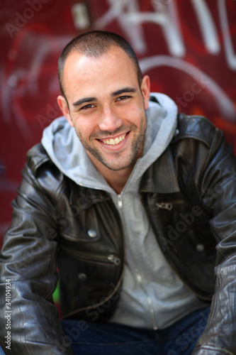 Smiling young man sitting in street