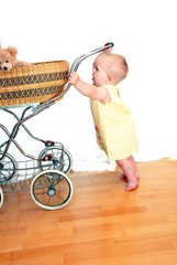 Child with doll's pram and yellow dress