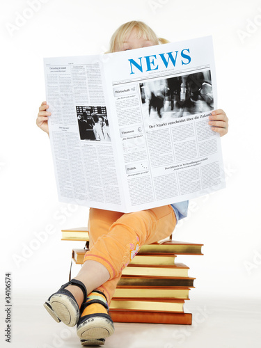 Little girl seated on books reading newspaper