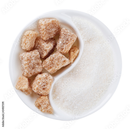 Brown lump cane sugar versus white one in Yang Yin shaped plate,