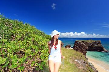 コマカ島の丘の上でひと休みしている笑顔の女性