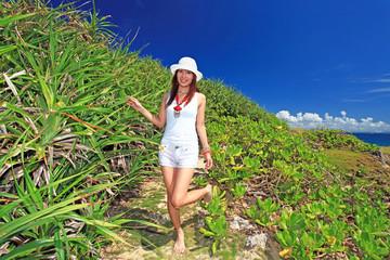コマカ島の亜熱帯植物と散歩を楽しむ笑顔の女性