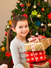 Young child holding gifts in front of Christmas tree