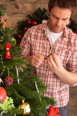 Young man fixing Christmas tree lights