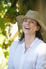 Beautiful mature woman wearing hat and laughing
