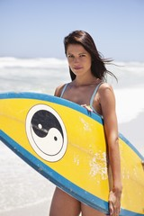 Portrait of a woman holding a surfboard on the beach
