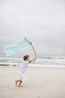 Boy running while holding flag on beach