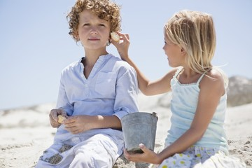 Girl holding shell to her brother's ear on beach