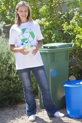 Portrait of a woman holding water bottles in hand beside recycling bin