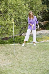 Young woman playing paddle ball in a garden